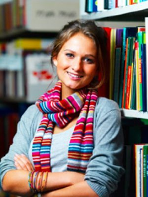 Young charming woman standing in library